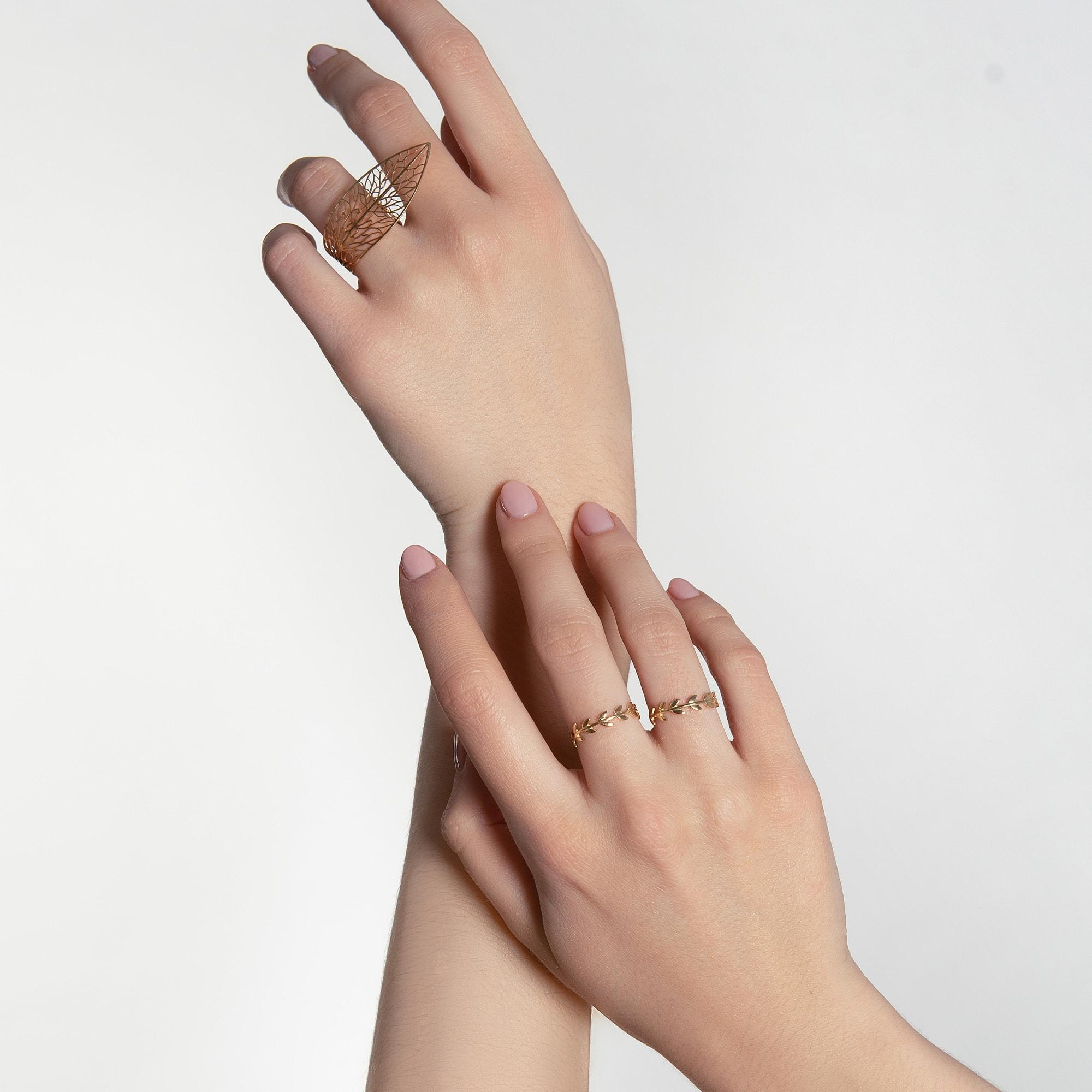 Mâini pe un un fundal bej cu inele din aur