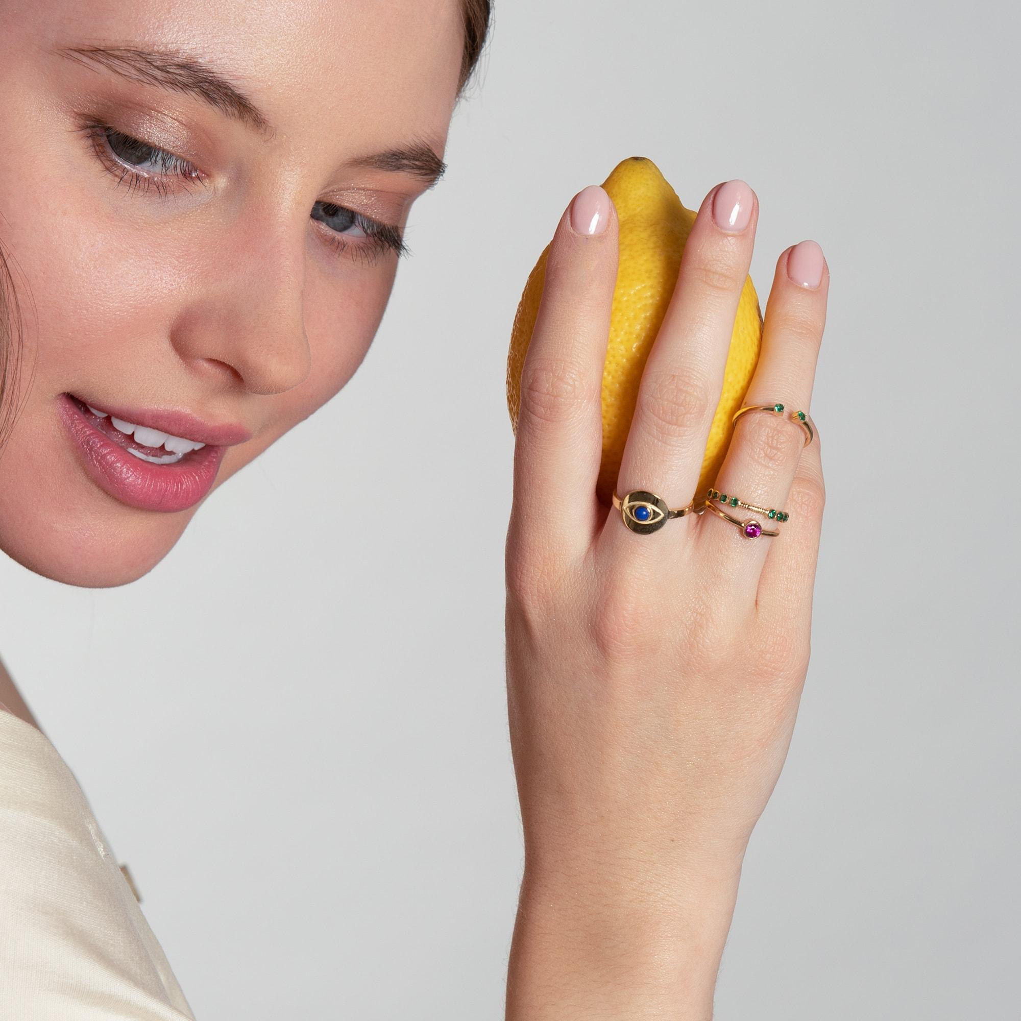 Tânără cu lămâie în mână și cu inele pe degete