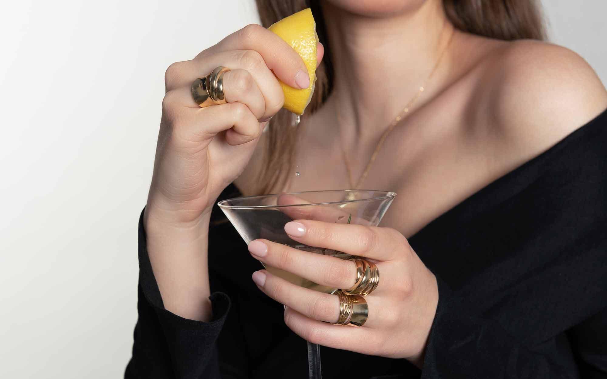 Tânără cu inele statement care stoarce lămâie într-un pahar de cocktail