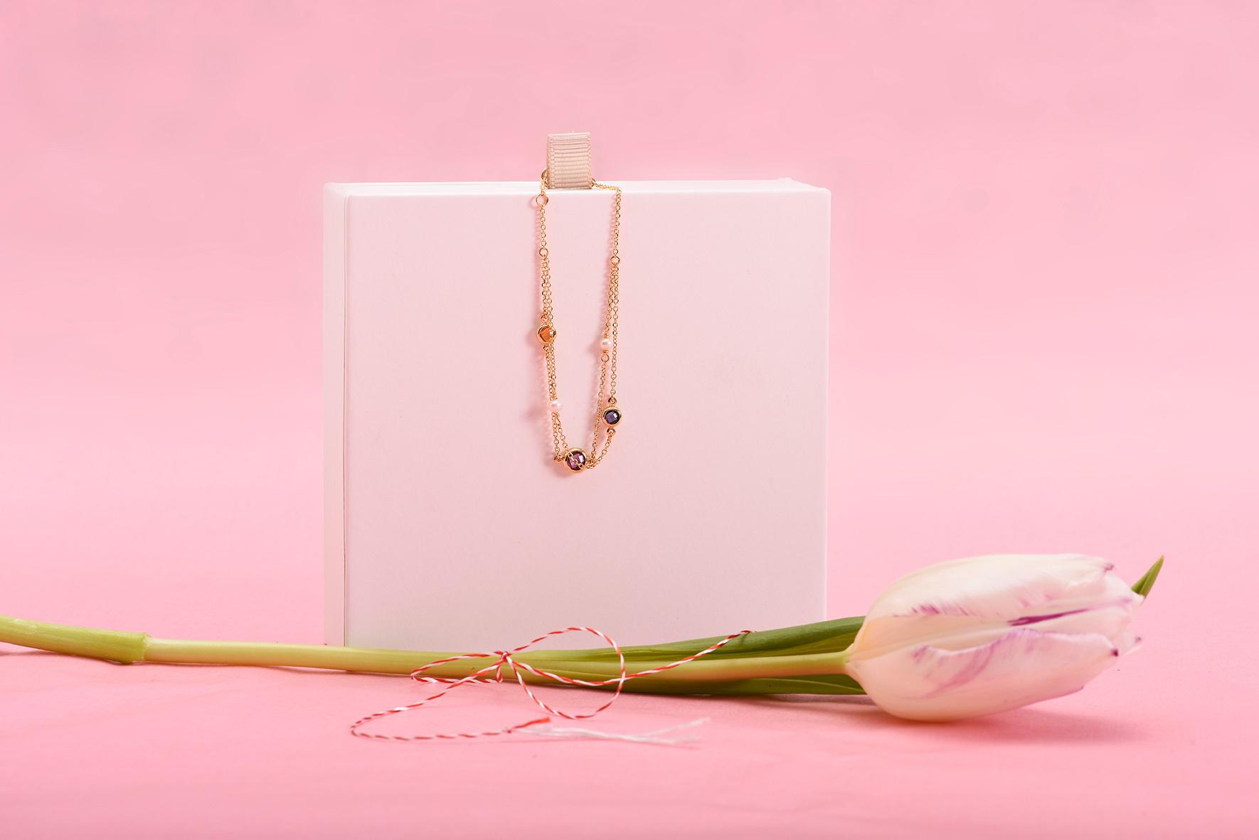 Aranjament pe fundal roz cu floare și brățară din aur