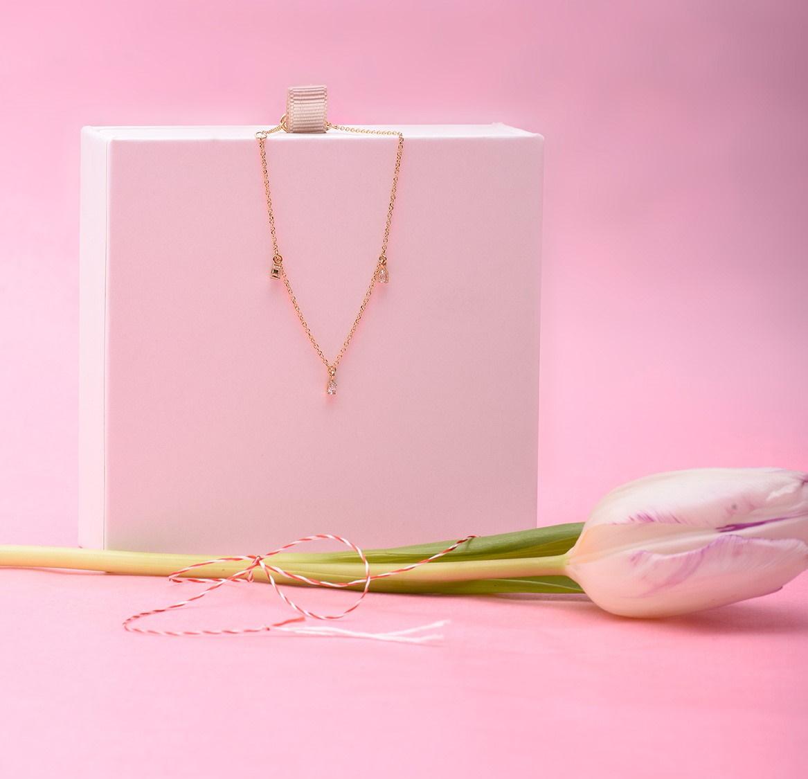 Aranjament pe fundal roz cu șnur de mărțișor, lalea și brățară din aur