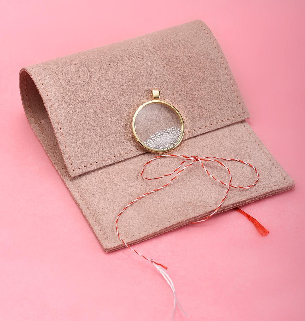 Aranjament pe fundal roz dintr-un plic din piele întoarsă, pandantiv din aur și șnur de mărțișor
