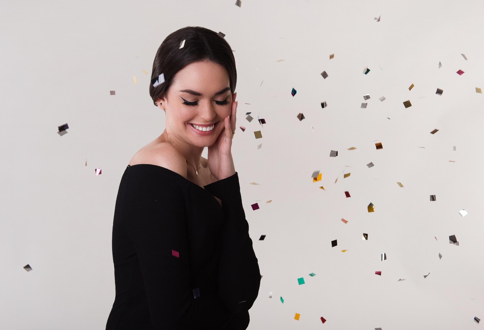 Tânără în bluză neagră care zâmbește, cu cercei în urechi și confetti