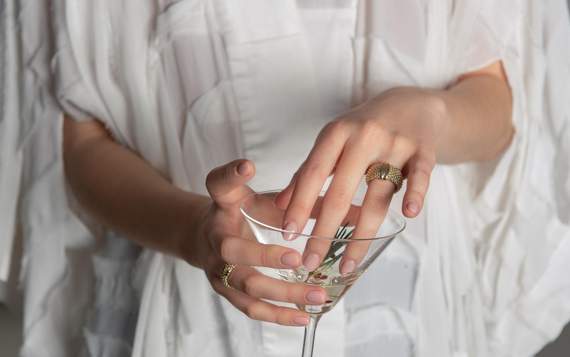 Mâini grațioase cu inele statement din aur pe degete și un pahar de cocktail