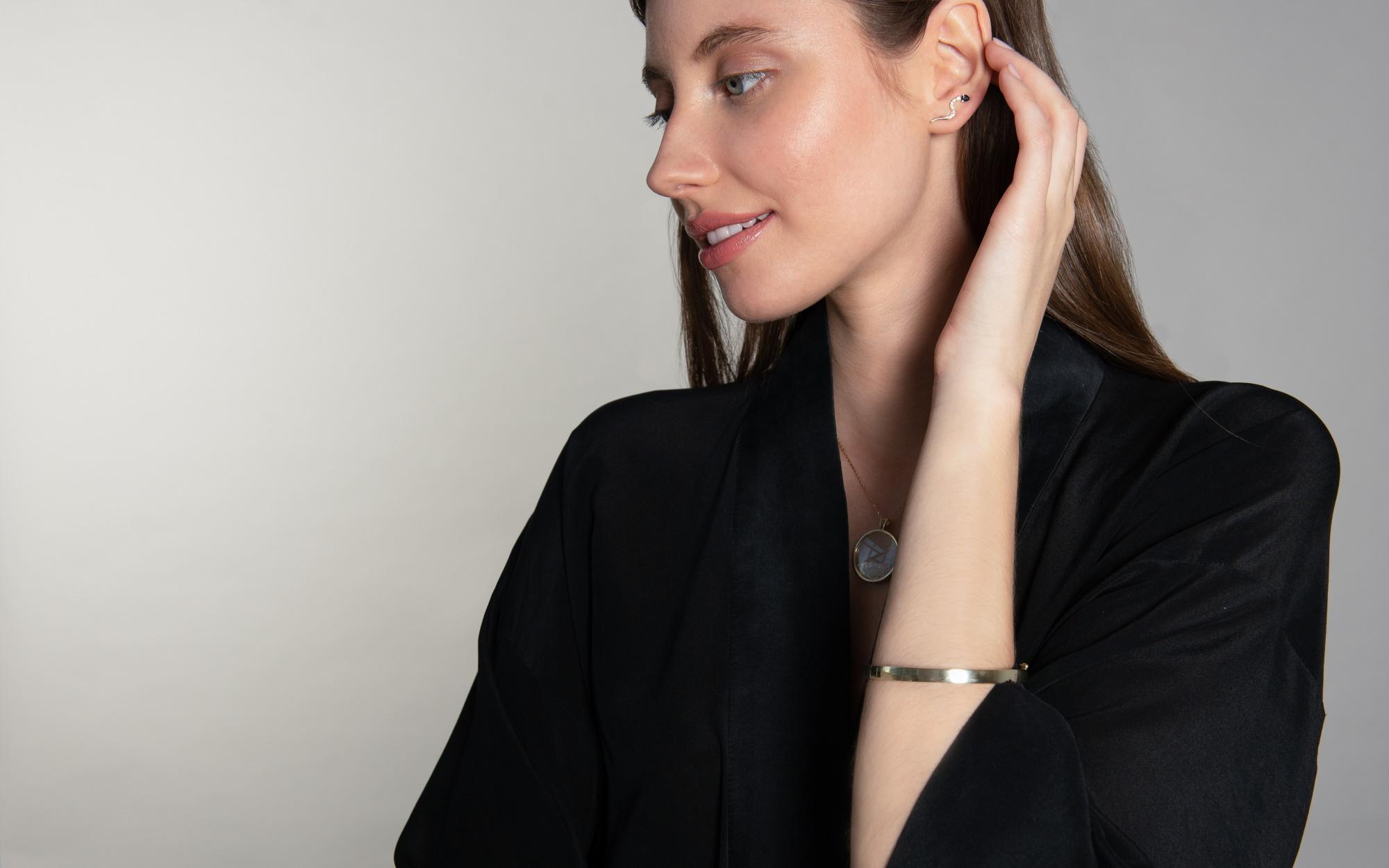 Tânără îmbrăcată în negru cu brățară din aur și cercei scurți la ureche